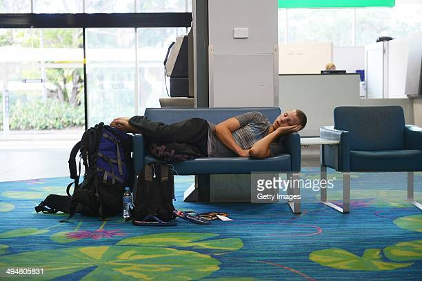A passenger sleeps in Darwin airport on May 31 2014 in Darwin Australia Flights in and out of Darwin have been suspended as volcanic ash from Mount...
