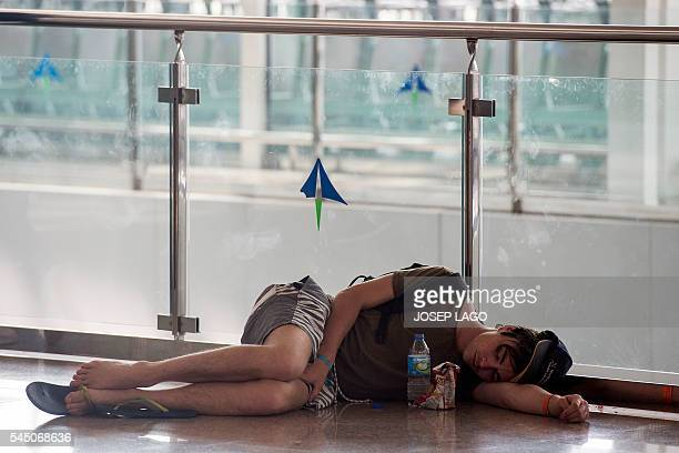 A passenger sleeps on the floor at the El Prat Airport in Barcelona on July 5 2016 Hundreds of passengers were left stranded today following the...