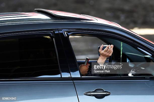 A passenger smokes while a driver uses a phone while behind the wheel of a car on April 30 2016 in New York City As accidents involving drivers using...