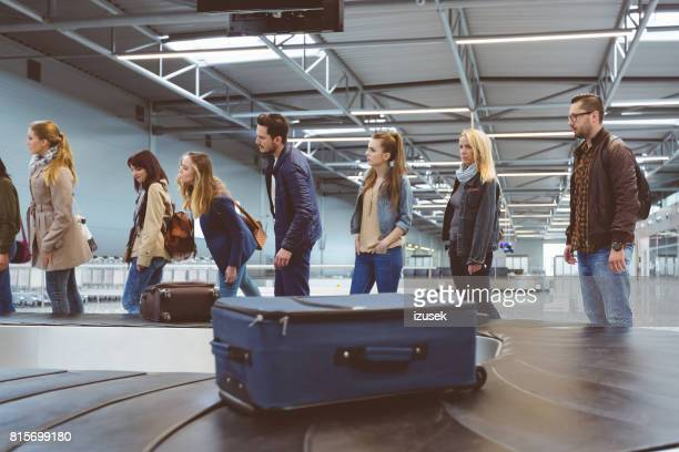 passenger standing at luggage conveyor belt in the airport - izusek stock pictures, royalty-free photos & images
