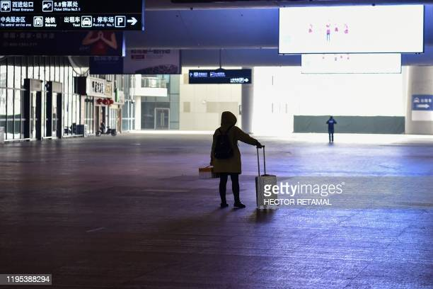TOPSHOT A passenger stands after arriving at the nearlydeserted Wuhan train station usually full of passengers ahead of the Lunar New Year in Wuhan...