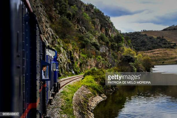A passenger stands by a window to observe the landscape from the Presidential Train during its trip to Douro north of Portugal on April 8 2018 Built...