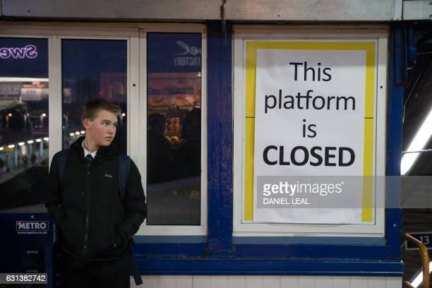 A passenger stands next to an information board informing passengers that a platform used by Southern Rail is closed at Clapham Junction station in...