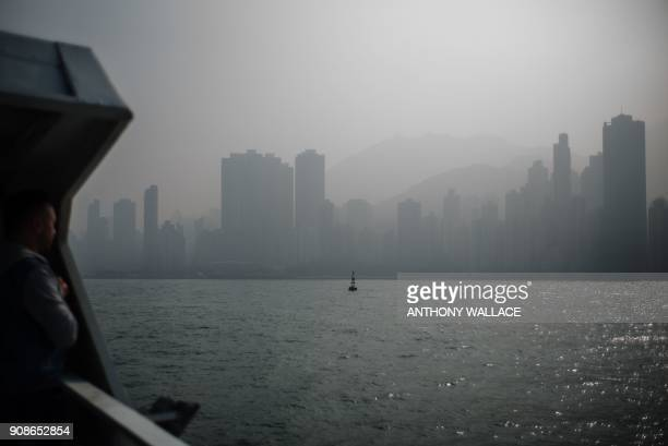 A passenger stands on the upper deck of a commuter ferry as smog engulfs residential and commercial buildings in Hong Kong on January 22 2018 Hong...