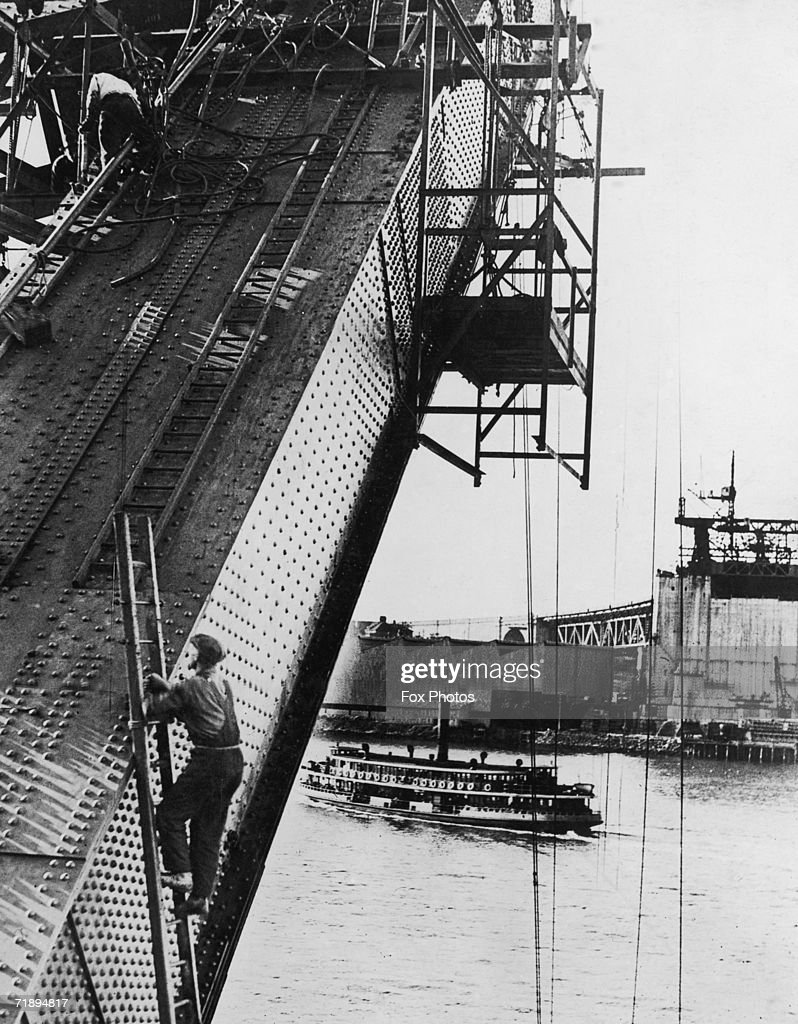 A passenger steamer passes under Sydney Harbour Bridge during the construction of its arch, circa 1930.