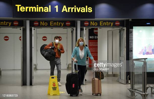 Passenger swearing PPE , including a face mask as a precautionary measure against COVID-19, push their suitcases after arriving at Terminal 1 of...