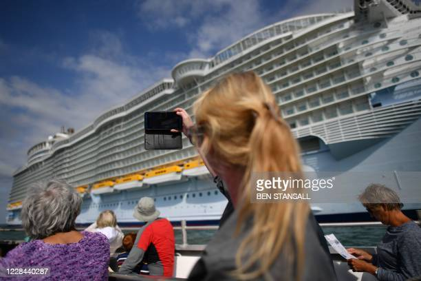 Passenger takes a picture of the cruise ship 'Allure of the Seas' during a Mudeford Ferry's cruise ship tour off the Dorset coast in southern England...