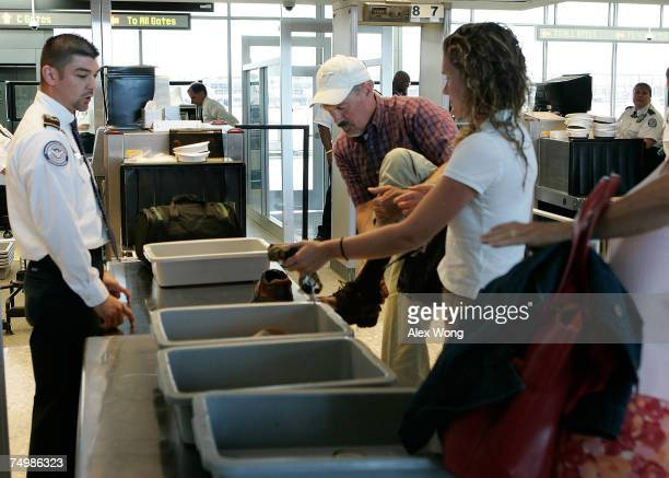 A passenger takes off his shoes as other passengers put their carryon luggage in trays for xray inspection before they pass through a security...