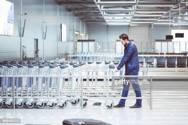 pkw unter einem gepäckwagen am flughafen terminal - izusek stock-fotos und bilder