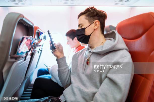passenger taking precautions - flying stock pictures, royalty-free photos & images