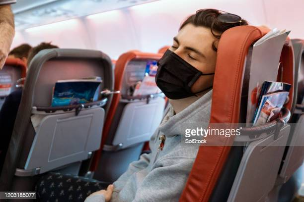passenger taking precautions - aeroplane stock pictures, royalty-free photos & images