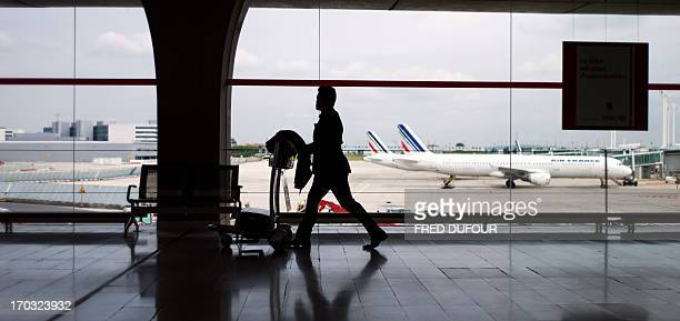 Passenger totes his bags at Roissy Charles de Gaulle international airport, in Roissy-en-France, outside of Paris on June 11, 2013. Hundreds of...
