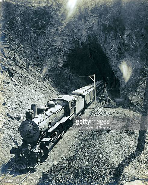 A passenger train is photographed coming out of a tunnel in a location somewhere in the Rocky Mountains circa 1920