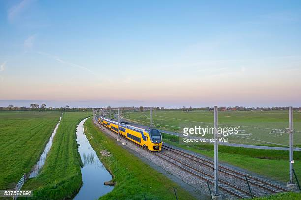 Passenger train of the Dutch Railways (NS) driving in a rural landscape