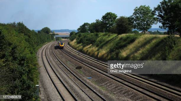 passenger train on curve through countryside - train vehicle stock pictures, royalty-free photos & images