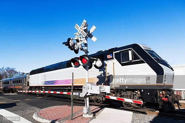 passenger train passing level crossing - railroad crossing stock pictures, royalty-free photos & images