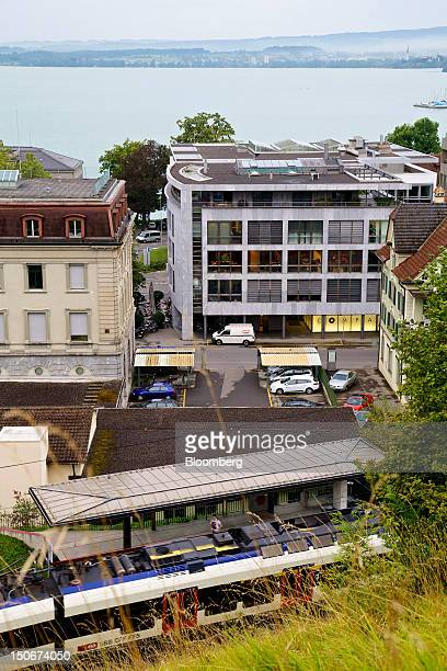 Passenger train waits by the platform at Postplatz station near the building that houses the headquarters of Xstrata Plc, center, in Zug,...