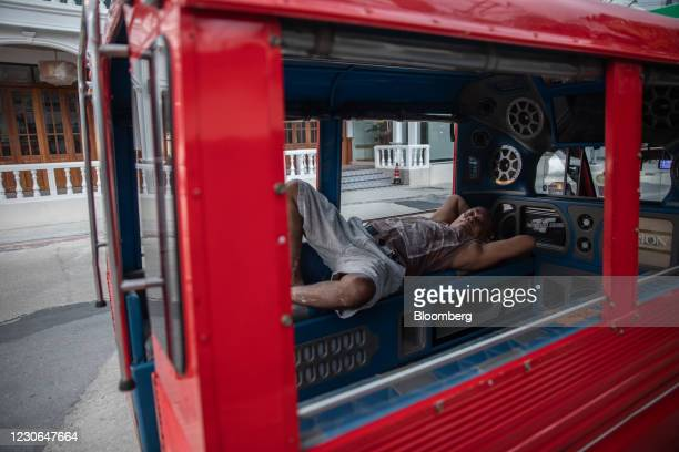 Passenger truck driver rests in his vehicle parked near Bangla Road in Patong, Phuket, Thailand, on Saturday, Dec. 19, 2020. The tepid response to...