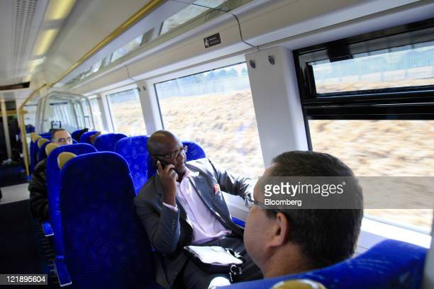 A passenger uses a mobile phone aboard a Gautrain passenger train en route from Johannesburg to OR Tambo International Airport near Johannesburg...