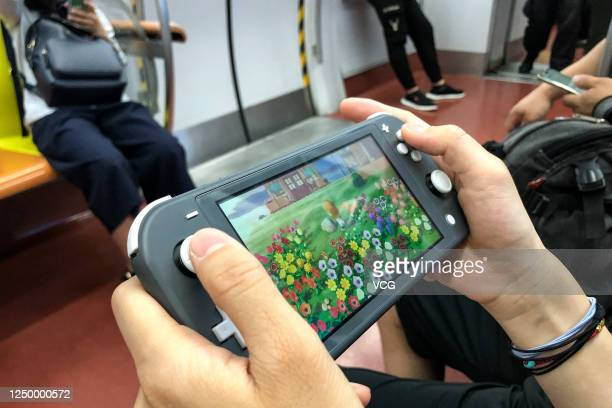 Passenger uses a Nintendo Switch to play video game 'Animal Crossing: New Horizons' on a subway train of Beijing Subway Line 1 on June 14, 2020 in...