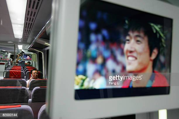 Passenger uses a phone on board the Airport Express train as China hurdle athlete Liu Xiang appears on TV on July 19, 2008 in Beijing, China. After...