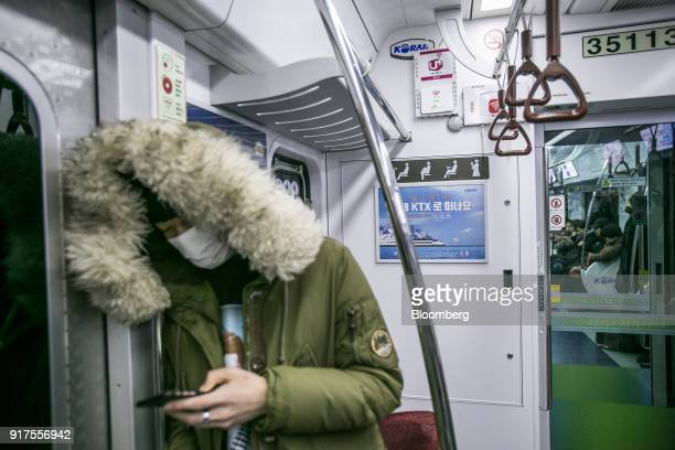 A passenger uses a smartphone near WiFi routers from LG Uplus Corp top left SK Telecom Co bottom left and KT Corp second left while riding in a...