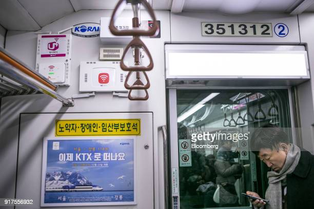 A passenger uses a smartphone next to WiFi routers from LG Uplus Corp top left SK Telecom Co bottom left and KT Corp right while riding in a subway...