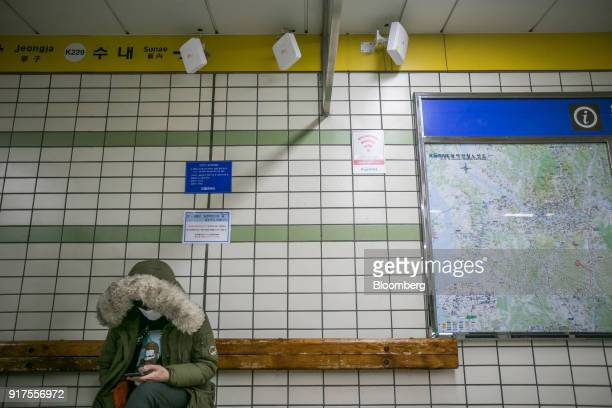 A passenger uses a smartphone while sitting under a sign for the KT Corp Olleh WiFi Giga internet service inside a subway station in Seongnam South...
