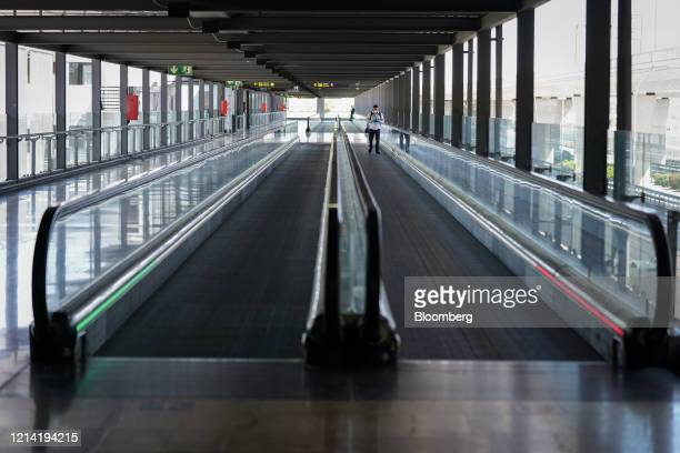 Passenger uses a travelator inside the departures terminal at Madrid Barajas airport, operated by Aena SA, in Madrid, Spain, on Wednesday, May 20,...