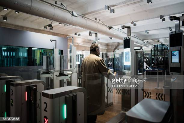 A passenger uses his biometric passport at an automated ePassport gate equiped with a facial recognition system at the British border of the Eurostar...