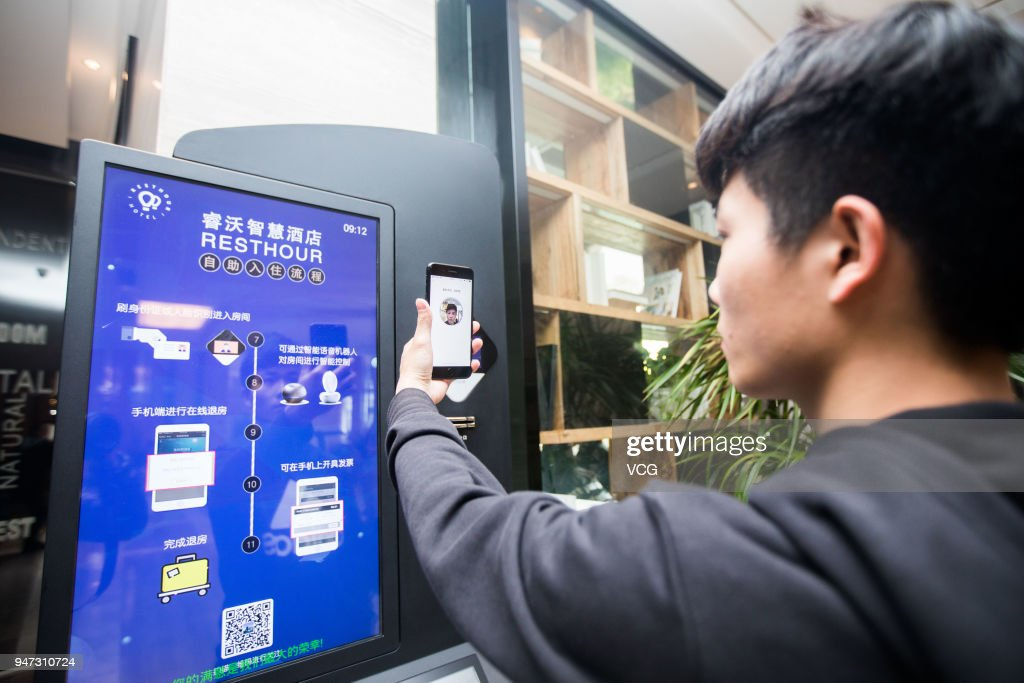 A passenger uses his 'electronic ID card' in the mobile payment app Alipay to verify himself as he checks in at a hotel on April 17, 2018 in Hangzhou, Zhejiang Province of China. 'Electronic ID card' will allow users to check in and go through security checks at railway stations and airports without showing their original ID cards and will be tested in Quzhou, Hangzhou and Fuzhou this April.