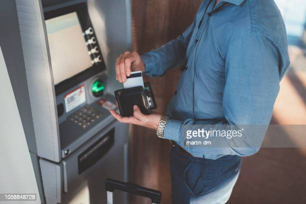 passenger using credit card at the atm on airport - bank account stock pictures, royalty-free photos & images