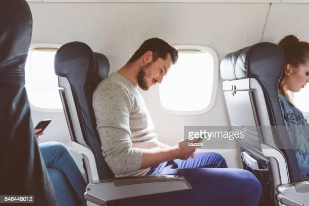 Passenger using mobile phone during flight