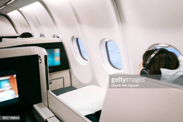 Passenger using on board entertainment on business class of  aircraft