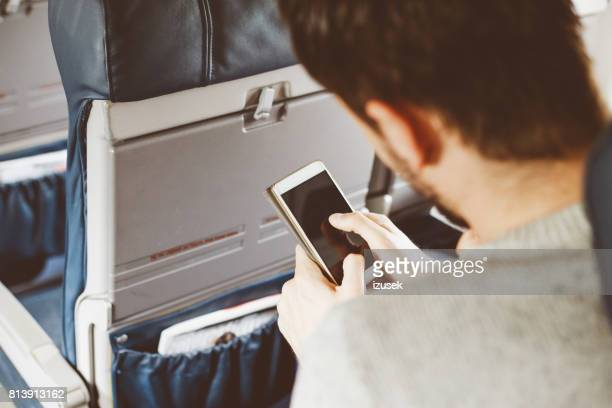 Passenger using smart phone while travelling by airplane