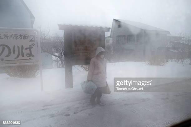 A passenger waiting for a Tsugaru Railways train on the platform of a train station is seen through a train window on February 1 2017 in Aomori Japan...