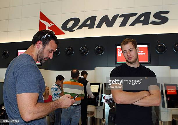 A passenger waiting to check in post's a message on facebook after hearing about the Qantas industrial action at Perth Domestic Terminal on October...