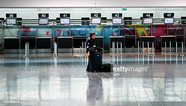 A passenger waits for checkin desks to open at Larnaca Airport on January 18 as Cyprus government services and airports came to a halt and thousands...