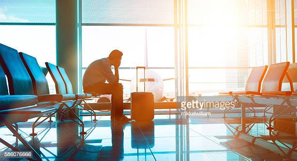passenger waits for plane in an airport - wachten stockfoto's en -beelden
