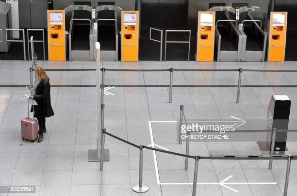A passenger waits in front of empty counters of German airline Lufthansa at the Lufthansa terminal of the Franz Josef Strauss airport in Munich...