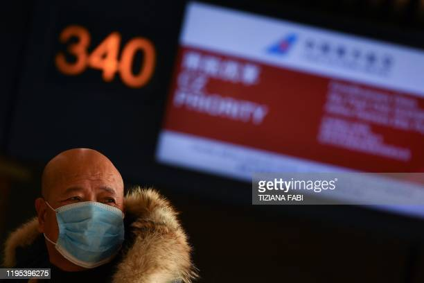 A passenger waits to checks in by the counter of China Southern Airlines at Rome's Fiumicino airport for a flight returning to Wuhan China after it...