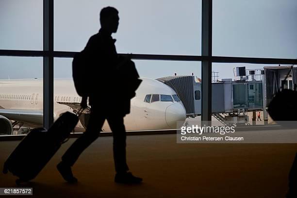 Passenger walking through airport terminal to aircraft