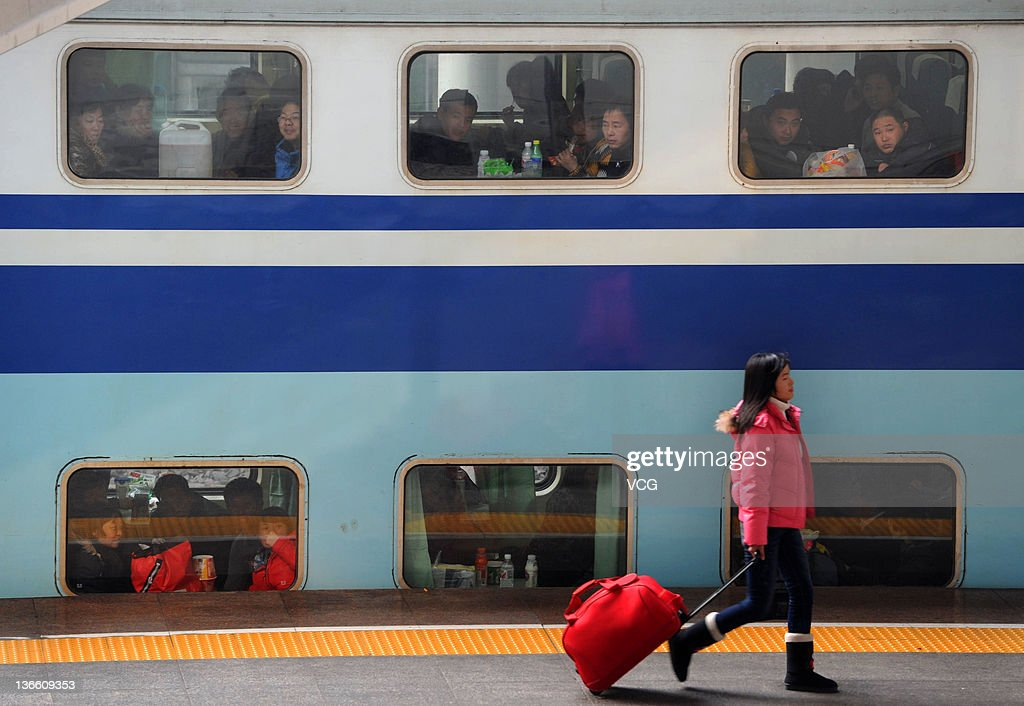 A passenger walks along a platform as a train is full of people at Hefei Railway Station on January 8, 2012 in Hefei, China. China's annual Spring Festival travel rush begins today as authorities estimate 3.158 billion passenger journeys will be made for the Chinese lunar new year during the 40-day travel period.