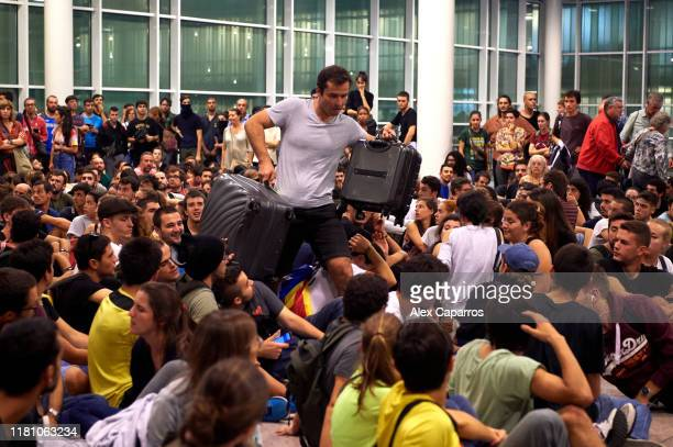 A passenger walks amongst protestors at the Barcelona Airport as thousands of protestors block the access in a protest following the sentencing of...