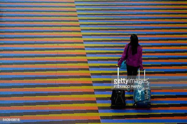 Passenger walks at Simon Bolivar international airport in Caracas, on June 17, 2016. German airline Lufthansa suspended flights to crisis-hit...