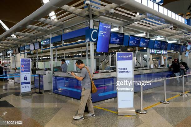 A passenger walks by the Malaysian Airline System Bhd checkin counters at Kuala Lumpur International Airport in Sepang Selangor Malaysia on Tuesday...