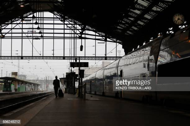 TOPSHOT A passenger walks on a platform at the Gare de Lyon railway station on June 1 2016 in Paris at the start of a strike by employees of French...