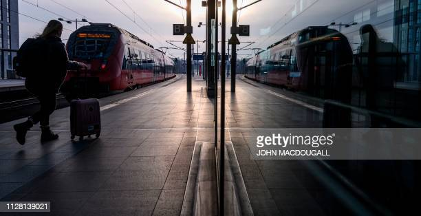 TOPSHOT A passenger walks on the platform as a regional train of the Deutsche Bahn pulls out of Berlin's main railway station on February 28 2019