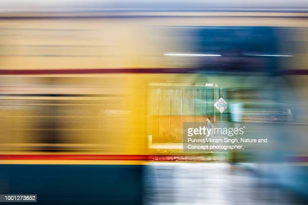 a passenger walks on the platform of local train station while another train passes by - moving past stock pictures, royalty-free photos & images