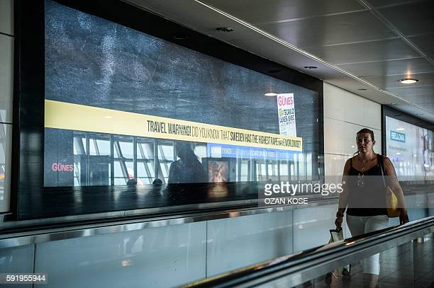 A passenger walks past a billboard advertisement reading 'Travel warning Do you know that Sweden has the highest rape rate worldwide' with an...